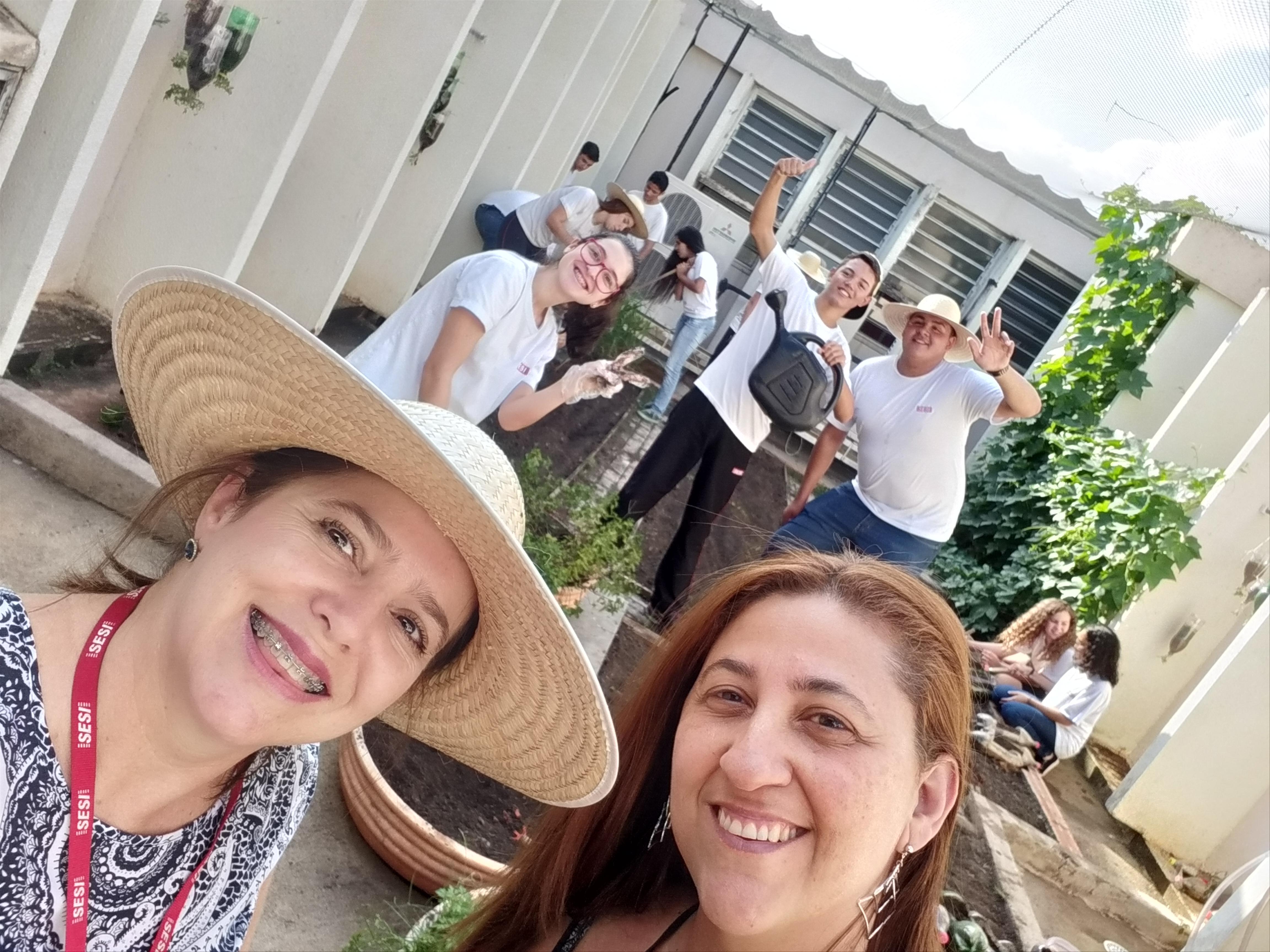 Nutricionista Rosilaine e Professora Ana Paula com alunos na horta da escola